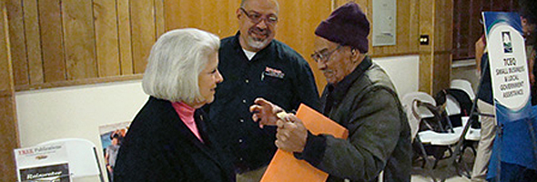 Senator Judith Zaffirini and Avelino Lino Garcia of the Texas Commission on Environmental Quality visit with a constituent at an open house in Kenedy.