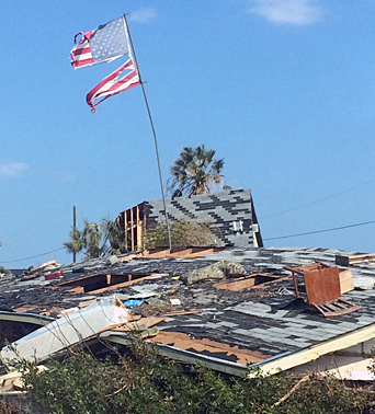 A tattered, windblown American flag stands defiantly amid the aftermath of Hurricane Harvey.