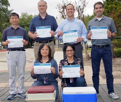 Thursday volunteers hold up their reasons for giving their time. Left to right-back row: Chuhua Tian, Erik Underkofler, Chance Goodin, and William Lara; front row: Candice Wong and Kanchan Raina.