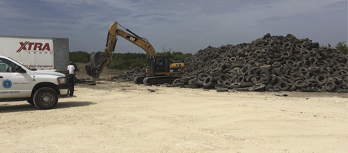An excavator loads scrap tires into a waiting truck as part of the multi-agency cleanup effort at the Gatesville scrap tire site where 268,000 scrap tires once littered the landscape.