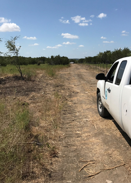 A TCEQ vehicle travels along a clear road that was once littered with scrap tires. Thanks to the multi-agency cleanup effort, the property is now free of scrap tires.