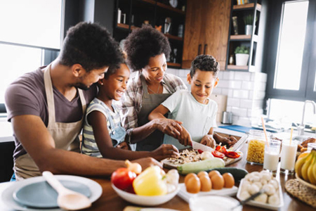 A family of four working together in the kitchen