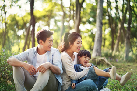 A family sitting together in a wooded area