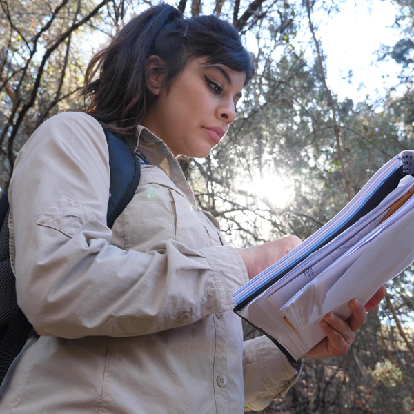 A woman examining documents out in the field
